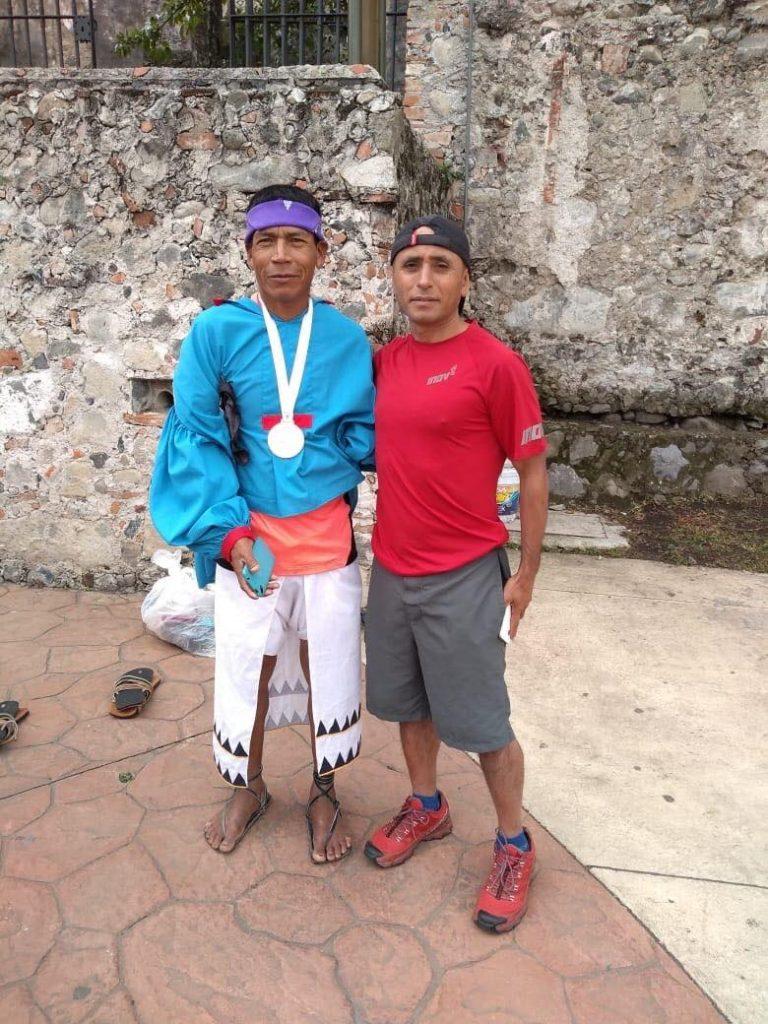 Vlevo je vítěz ultramaratonu v typických běžeckých sandálech...